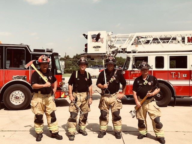 Firefighters of C shift pose with tools
