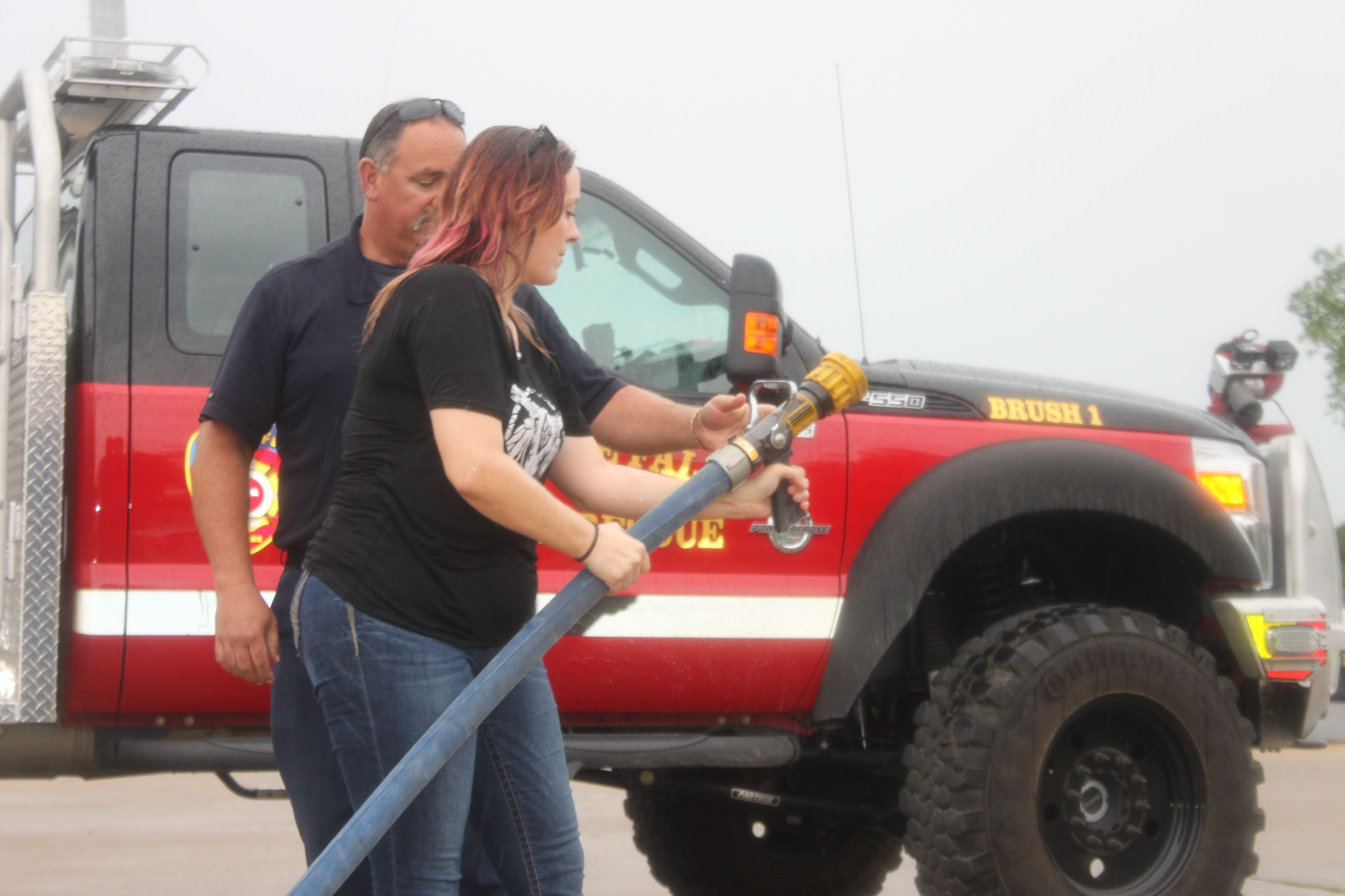 A firefighter teaches someone how to use a fire hose