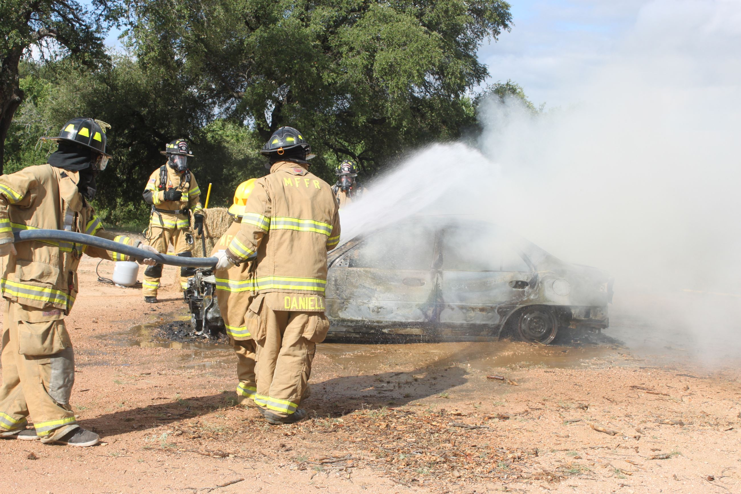 Firefighters use hoses on a burning car