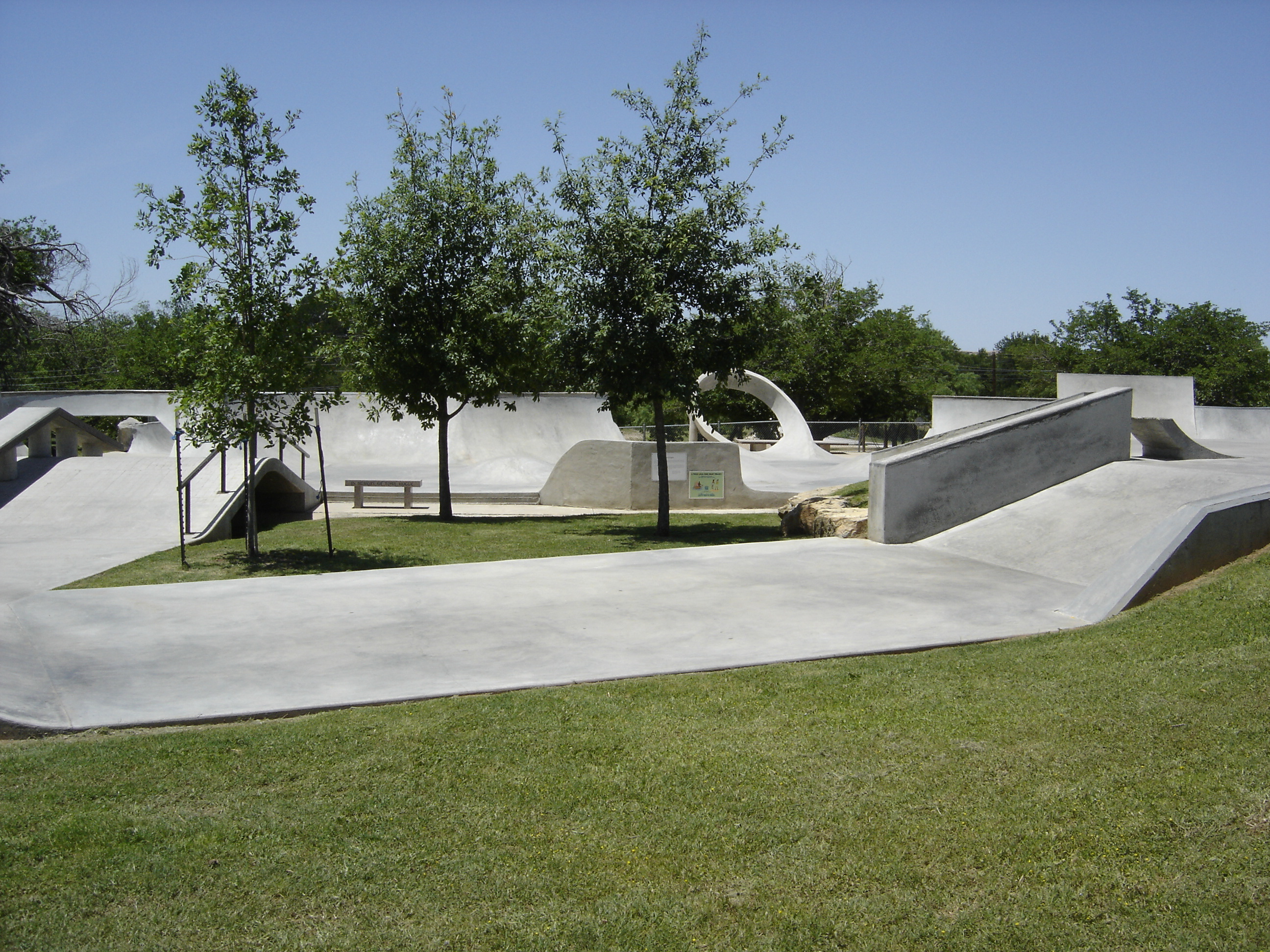 Grassy area with trees in the center of the skate park.